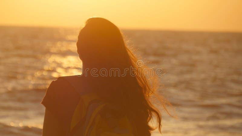 Mujer joven del viajero que se coloca en orilla del océano y que mira salida del sol Turista femenino joven con la mochila que di foto de archivo libre de regalías