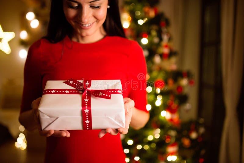 Mujer joven delante del árbol de navidad que da el presente imagenes de archivo