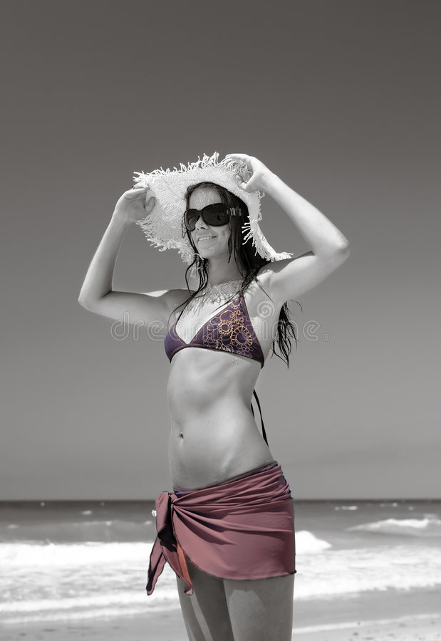 Mujer joven delgada, atractiva que ajusta el sombrero de paja en la playa asoleada imagen de archivo