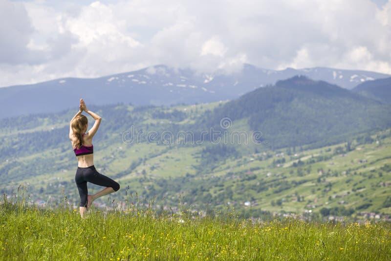 Mujer joven delgada atractiva que hace ejercicios de la yoga al aire libre en el fondo de montañas verdes en día de verano solead foto de archivo libre de regalías