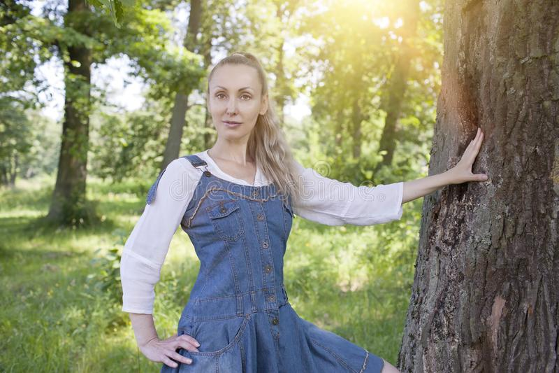 Mujer joven delgada hermosa en sundress azules y una blusa blanca cerca de un tronco de árbol en el bosque solar imagen de archivo