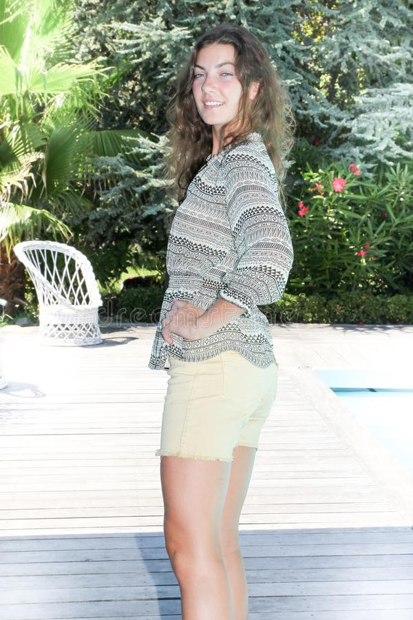 Mujer joven delgada hermosa que se coloca cerca de la piscina foto de archivo libre de regalías