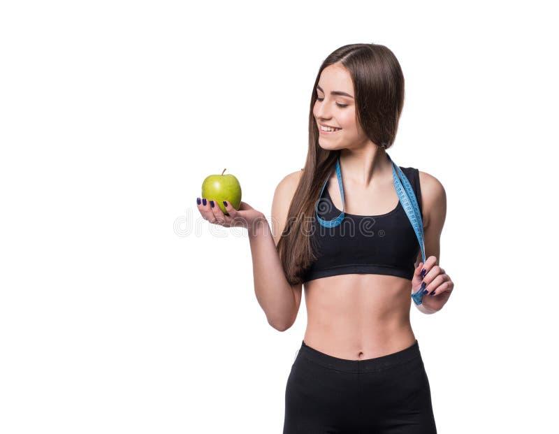 Mujer joven delgada y sana que sostiene la cinta de la medida y manzana aislada en el fondo blanco Pérdida de peso y concepto de  imagen de archivo