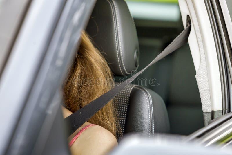 Mujer joven dentro del vehículo que lleva el cinturón de seguridad protector Concepto de la seguridad y de la precaución fotos de archivo