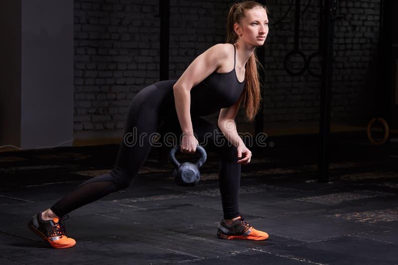 Mujer joven deportiva con el cuerpo muscular que hace entrenamiento del crossfit con el kettlebell en fondo oscuro fotos de archivo