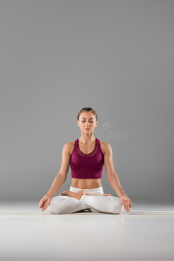 mujer joven deportiva con los ojos cerrados que meditan en la posición de loto foto de archivo libre de regalías