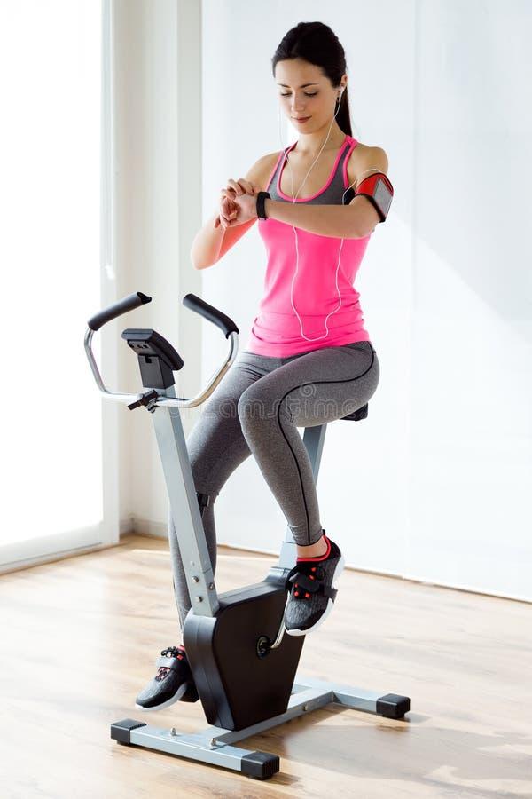 Mujer joven deportiva hermosa que hace ejercicio en gimnasio imagen de archivo