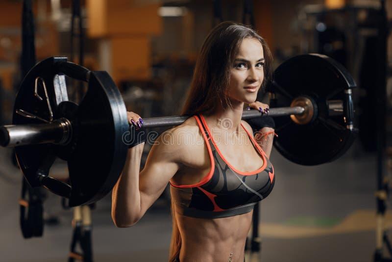 Mujer joven deportiva que ejercita con el barbell en gimnasio Deporte, aptitud, el powerlifting y concepto de la gente imagenes de archivo