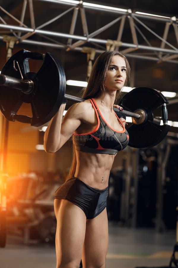 Mujer joven deportiva que ejercita con el barbell en gimnasio Deporte, aptitud, el powerlifting y concepto de la gente foto de archivo