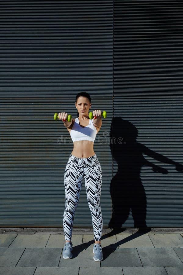 Mujer joven deportiva que lleva a cabo los pesos que se colocan en fondo negro de la pared en la puesta del sol fotografía de archivo