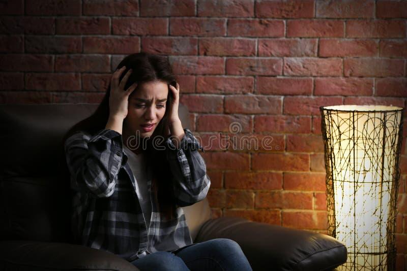 Mujer joven deprimida en fondo del ladrillo imagen de archivo libre de regalías