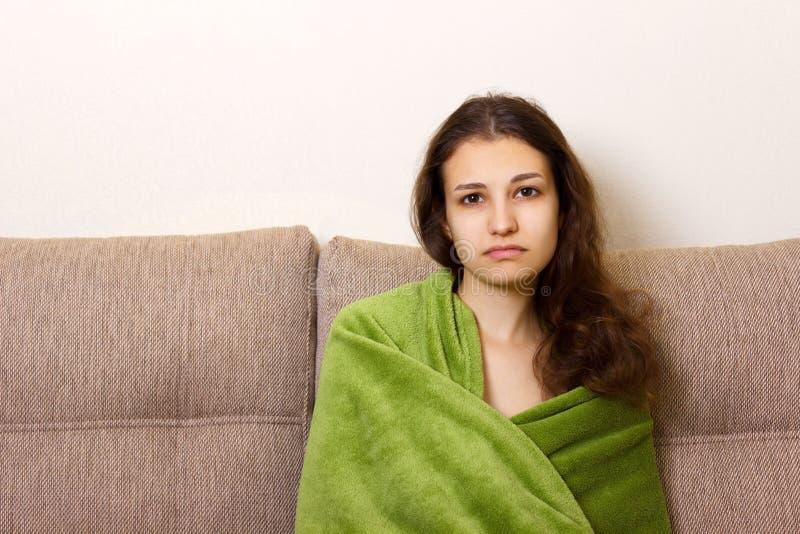 Mujer joven deprimida que se sienta en el sofá La muchacha adolescente subrayada y trastornada siente el vacío emocional, soledad fotos de archivo libres de regalías
