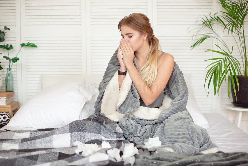 Mujer joven desgraciada que se sienta en la cama envuelta en enfermo combinado caliente de la sensación con gripe fotografía de archivo