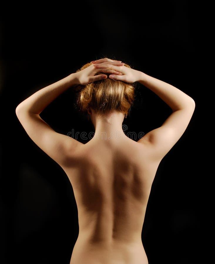 Mujer joven desnuda de la parte posterior con los brazos levantados fotos de archivo libres de regalías