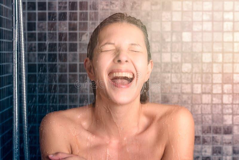 Mujer joven desnuda feliz que toma la ducha fotografía de archivo libre de regalías