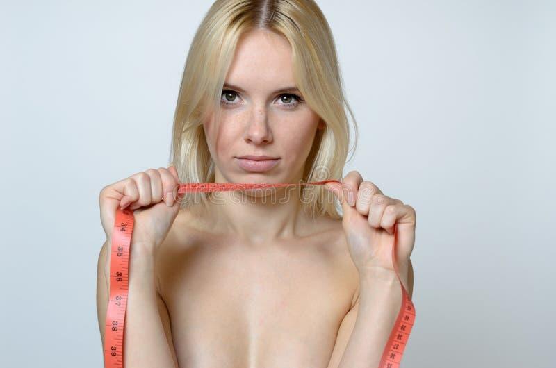 Mujer joven desnuda que detiene a una cinta métrica fotos de archivo libres de regalías