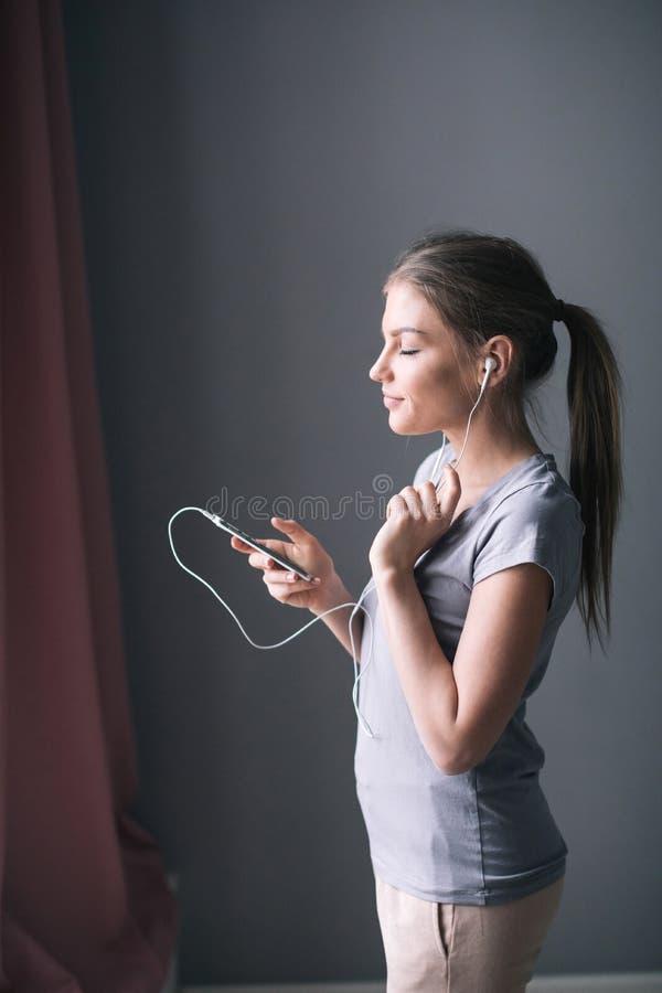Mujer joven despreocupada feliz que escucha la música del smartphone sobre fondo gris imagenes de archivo