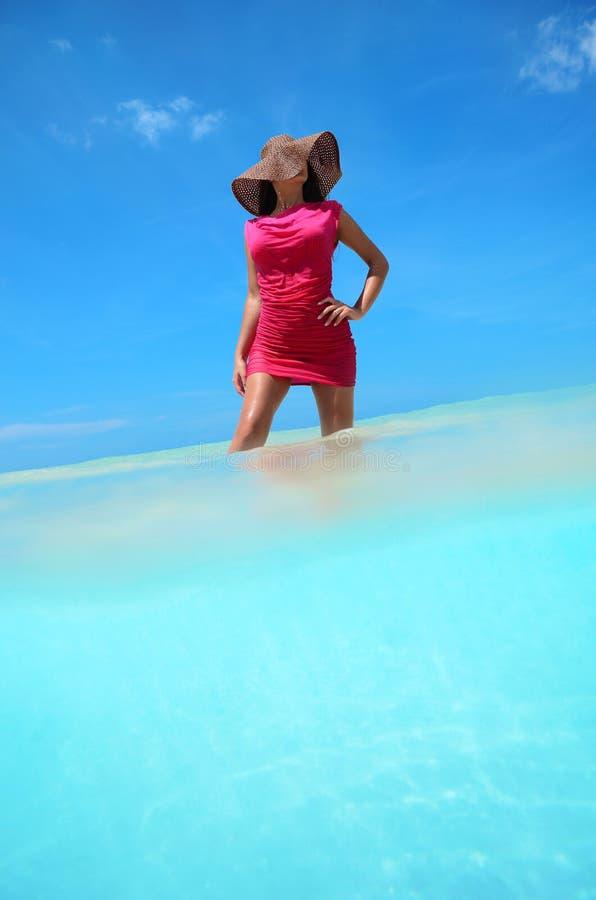 Mujer joven despreocupada que goza del agua tropical clara fotos de archivo libres de regalías