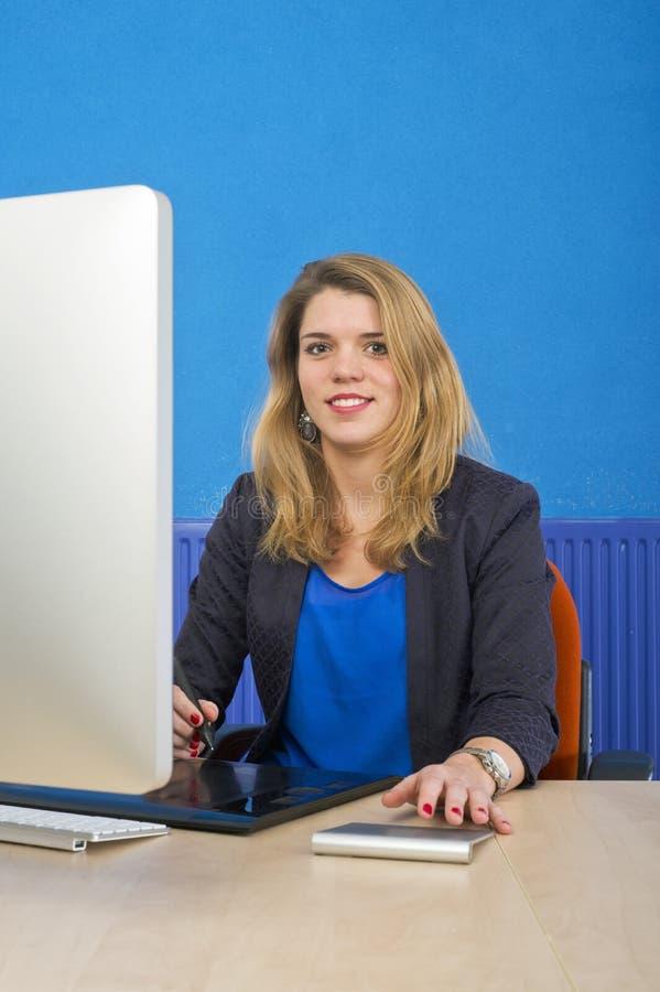 Mujer joven detrás de un ordenador imagenes de archivo