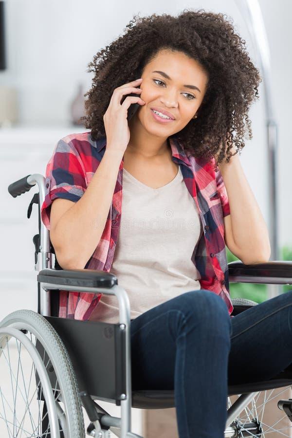 Mujer joven discapacitada en el teléfono foto de archivo