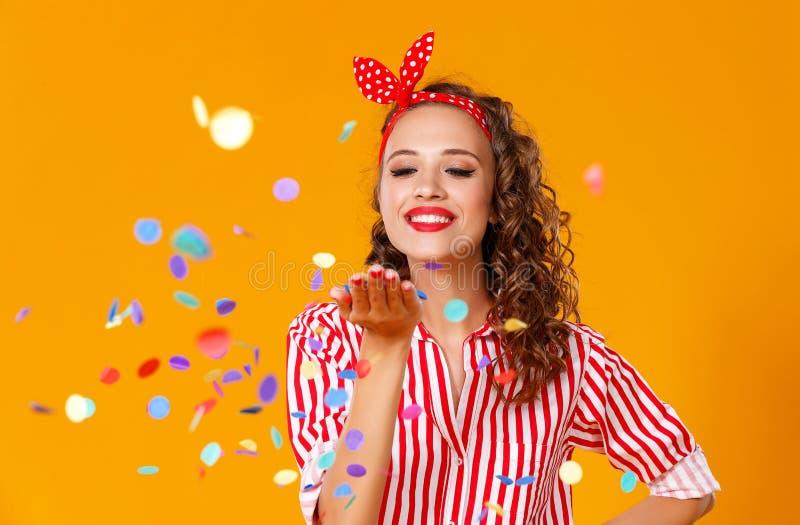Mujer joven divertida alegre con confeti festivo en amarillo imagen de archivo libre de regalías