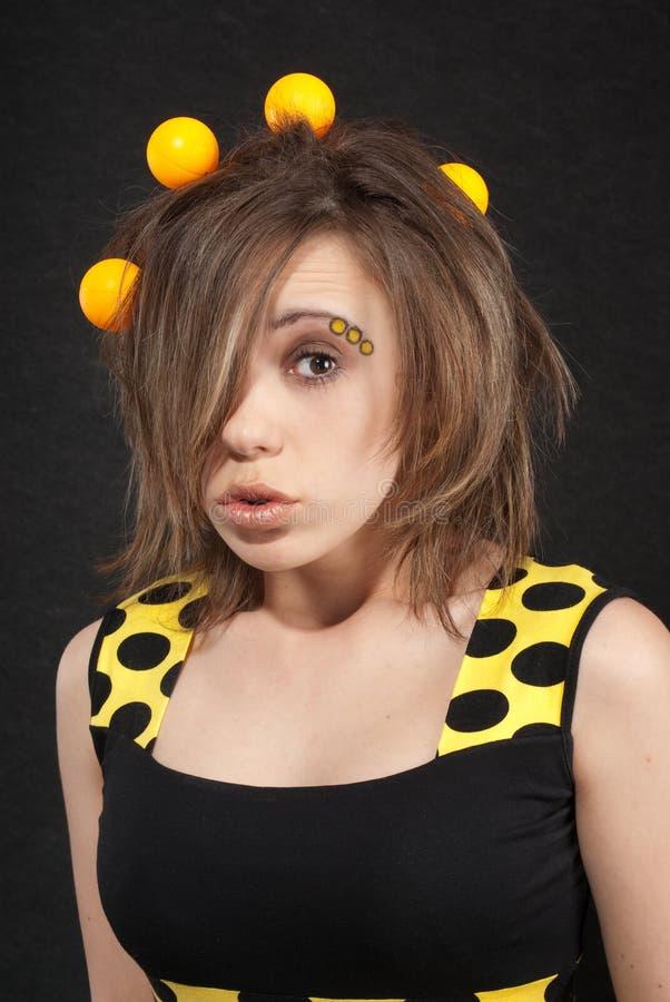Mujer joven divertida en estudio con las bolas amarillas fotografía de archivo