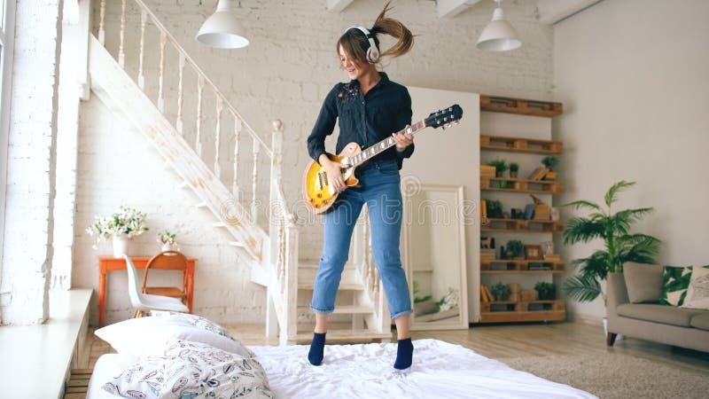 Mujer joven divertida en los auriculares que saltan en cama con la guitarra eléctrica en dormitorio en casa dentro fotografía de archivo