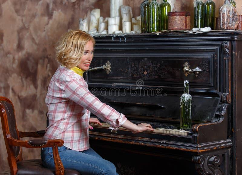 Mujer joven divertida que juega el piano retro lamentable imagen de archivo