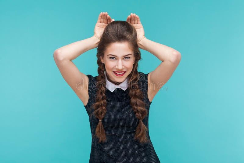 Mujer joven divertida que muestra la muestra y la sonrisa del conejo fotos de archivo libres de regalías