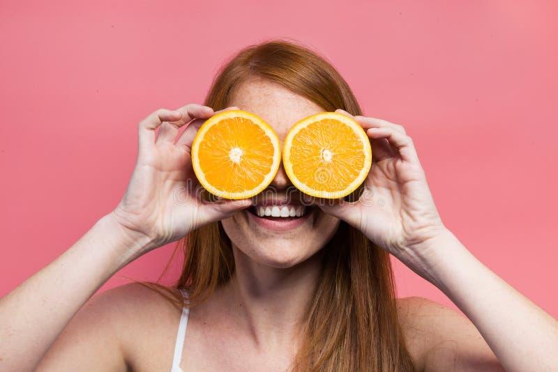 Mujer joven divertida que presenta con las rebanadas anaranjadas sobre fondo rosado imagen de archivo