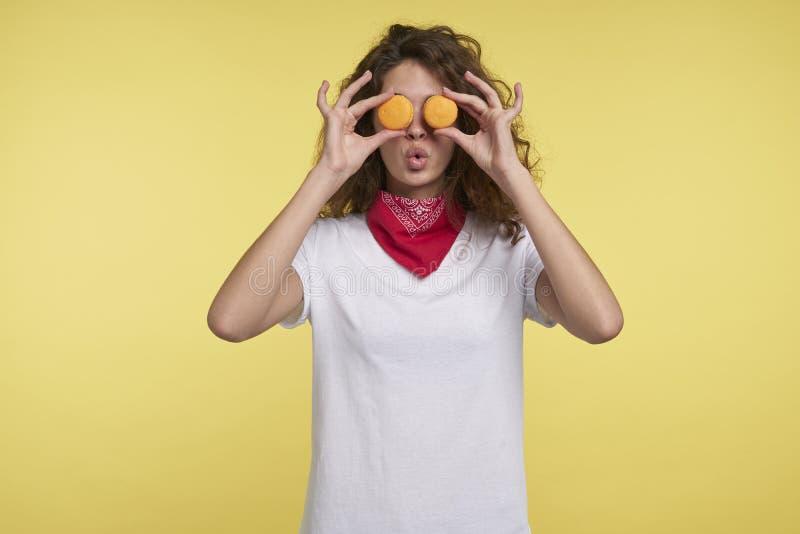 Mujer joven divertida que sostiene los macarrones cerca de ojos, contra fondo amarillo imagenes de archivo