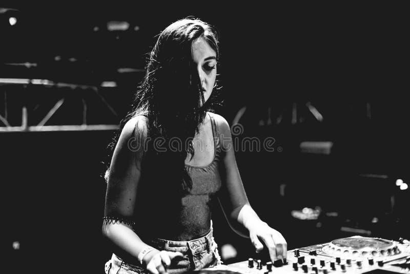 Mujer joven DJ que juega música en el festival de la noche de verano Concepto de la diversión, de la juventud, del entretenimient foto de archivo