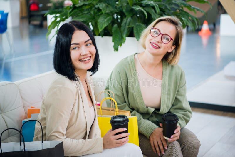 Mujer joven dos que charla en una cafetería fotos de archivo