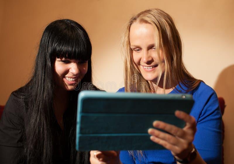 Mujer joven dos que lee una tableta-PC fotografía de archivo