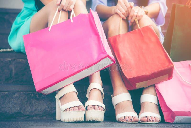 Mujer joven dos que se sienta con compras del bolso en las escaleras después de hacer compras en la alameda foto de archivo