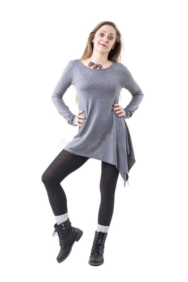 Mujer joven dudosa escéptica con los brazos en las caderas que miran la cámara foto de archivo