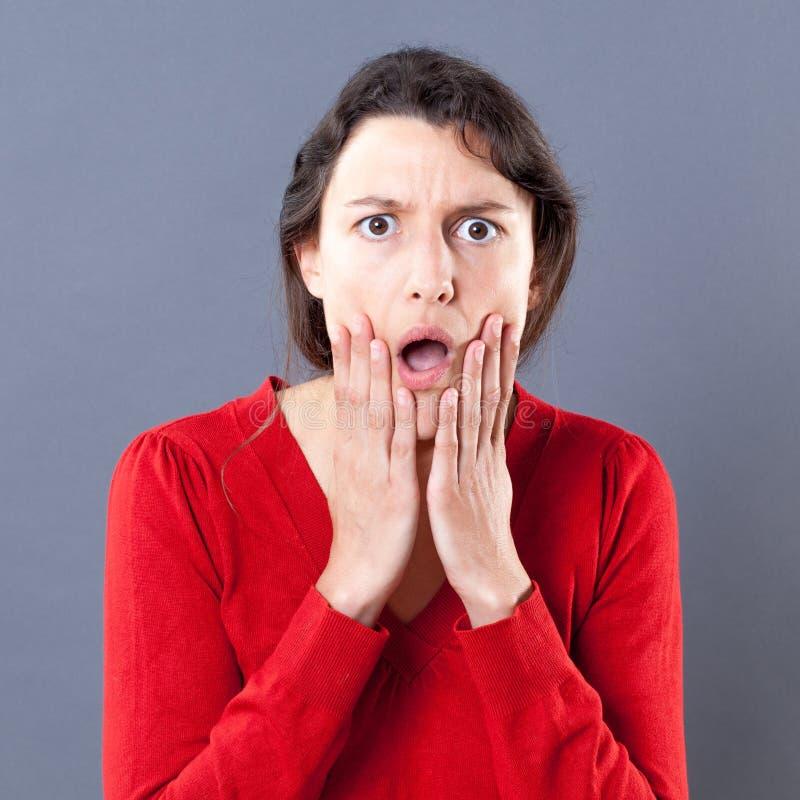 Mujer joven Dumbstruck con la expresión de caída del mandíbula que toca su cara fotografía de archivo libre de regalías
