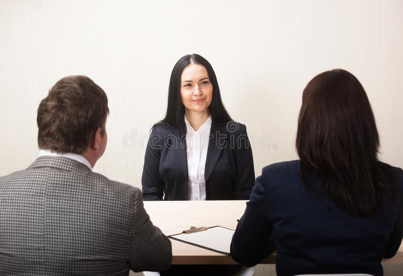 Mujer joven durante entrevista de trabajo y miembros de managemen imagen de archivo