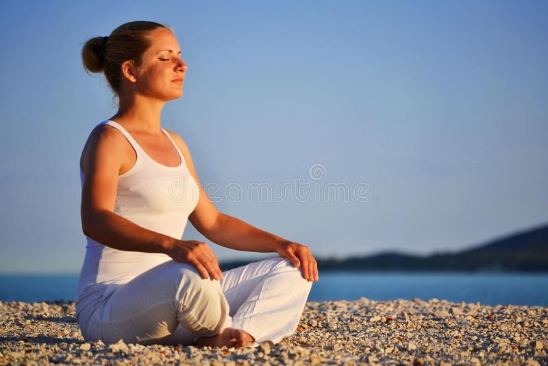 Mujer joven durante la meditación de la yoga en la playa fotos de archivo