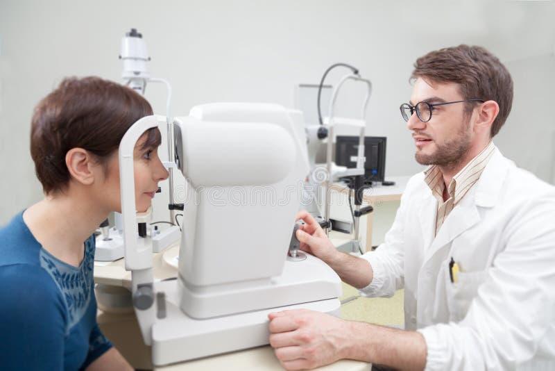 Mujer joven durante un examen de la vista con el oftalmólogo fotografía de archivo