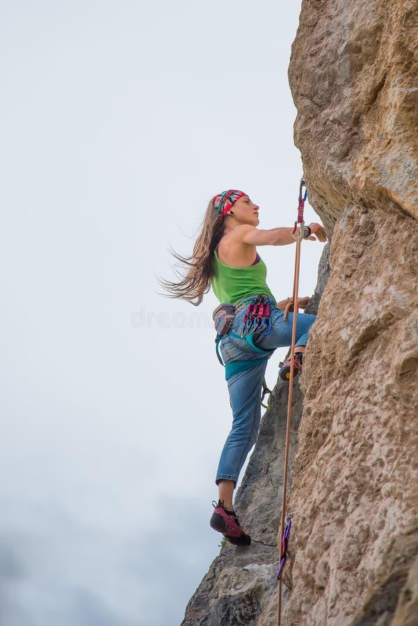 Mujer joven durante una aventura de la escalada imagenes de archivo