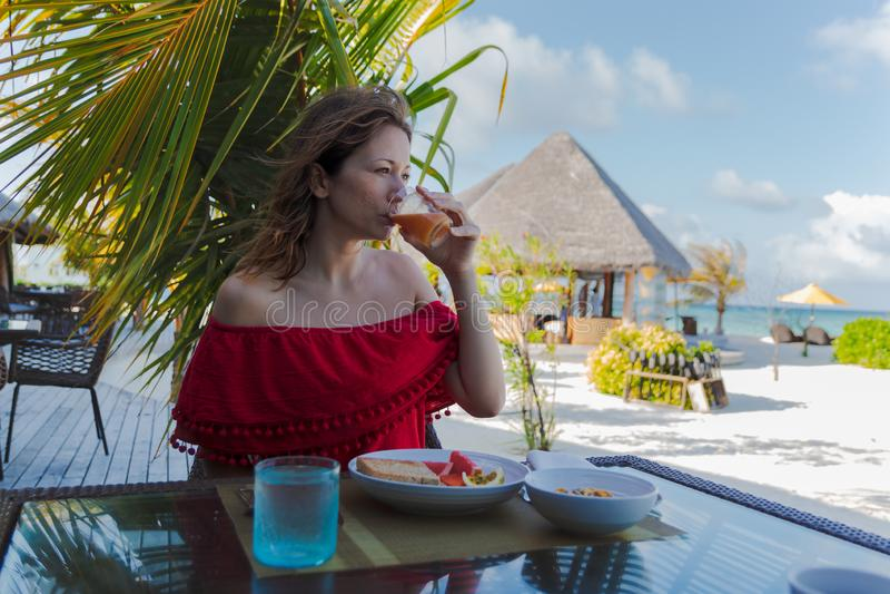 Mujer joven el d?a de fiesta en una isla tropical que come un desayuno sano imágenes de archivo libres de regalías