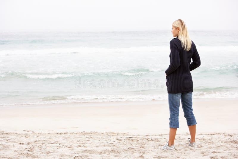 Mujer joven el el día de fiesta que se coloca en la playa del invierno imagenes de archivo