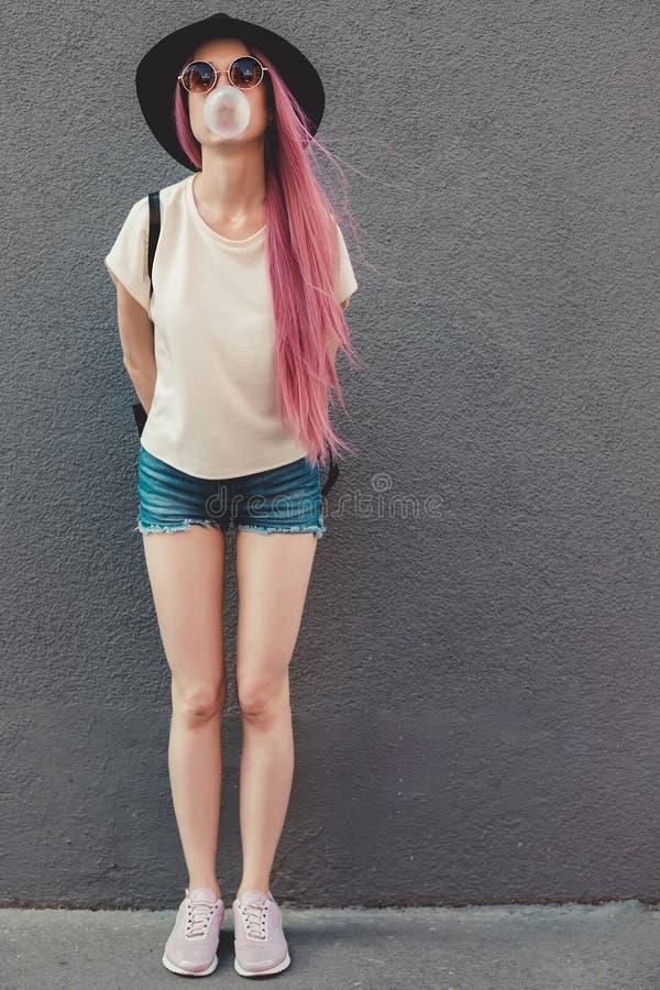 Mujer joven elegante del inconformista con el pelo rosado largo que sopla una burbuja con el chicle fotos de archivo libres de regalías