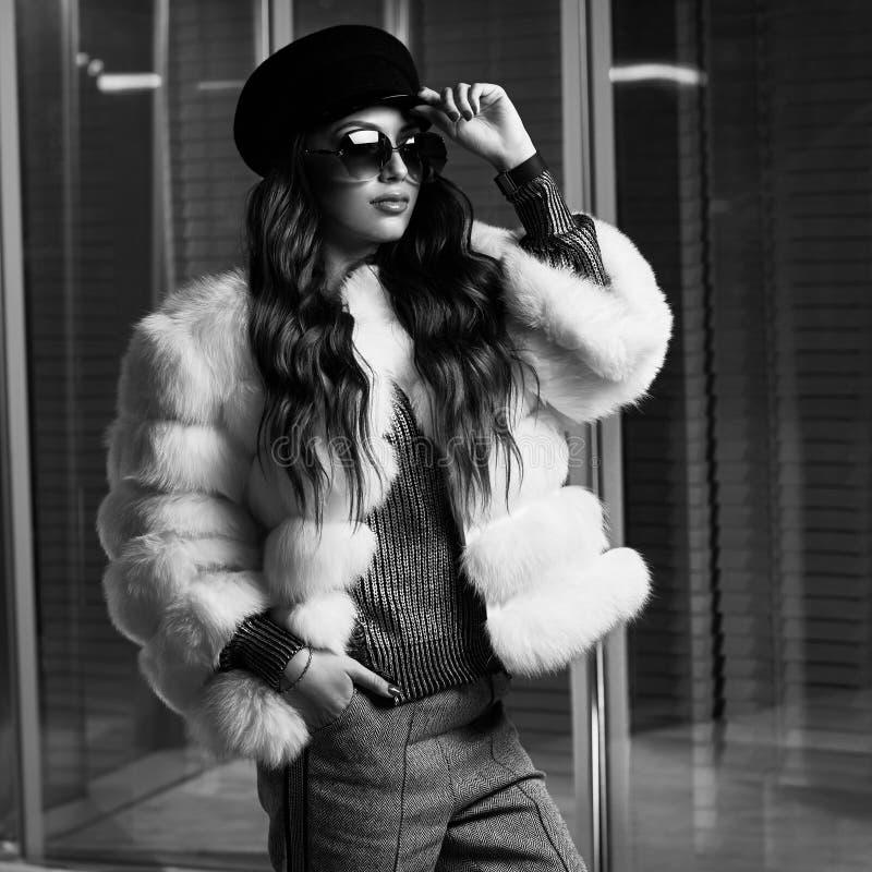 Mujer joven elegante en el abrigo de pieles blanco y gafas de sol redondas fotografía de archivo
