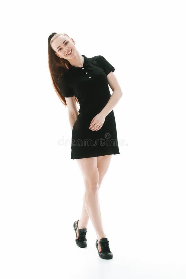 Mujer joven elegante en el peque?o vestido corto que mira la c?mara Aislado en el fondo blanco fotografía de archivo libre de regalías