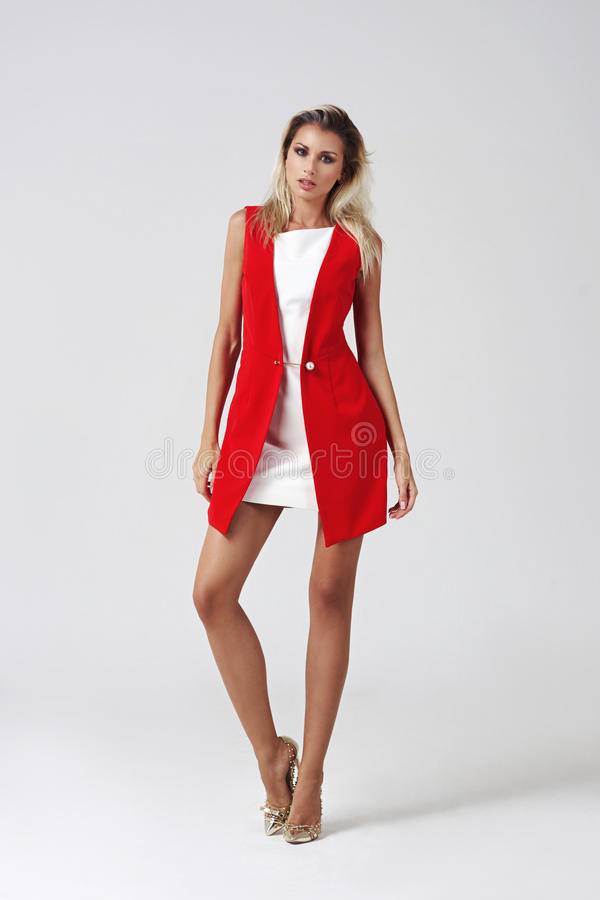 Mujer joven elegante en el vestido blanco y la chaqueta roja imagen de archivo