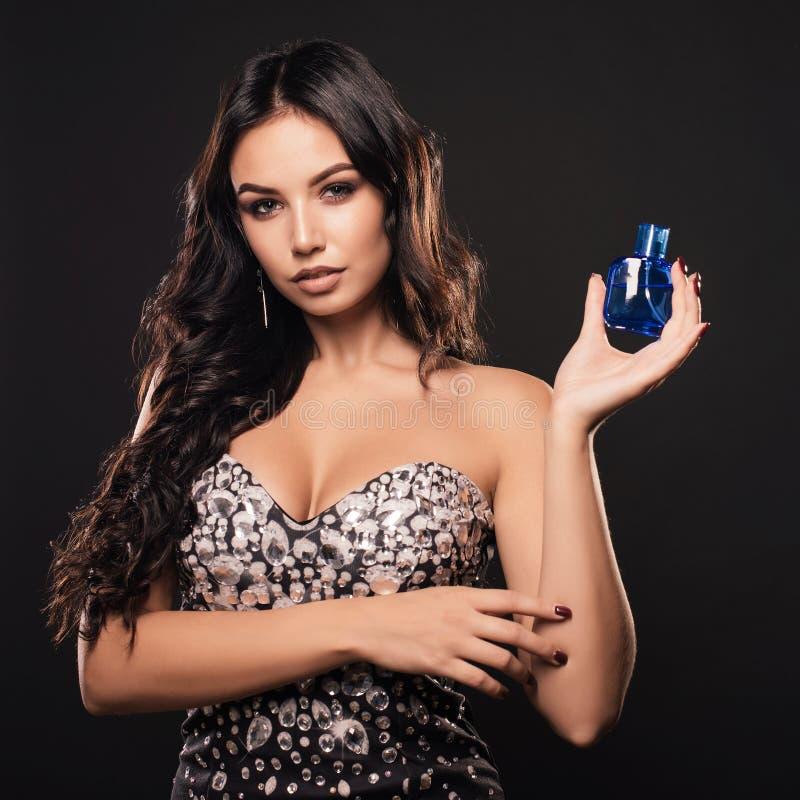 Mujer joven elegante en un vestido hermoso con perfume en fondo oscuro fotografía de archivo