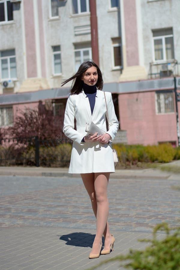 Mujer joven elegante en una calle de la ciudad con un periódico en sus manos imagen de archivo