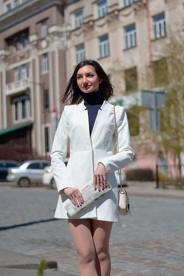 Mujer joven elegante en una calle de la ciudad con un peri?dico en sus manos fotos de archivo